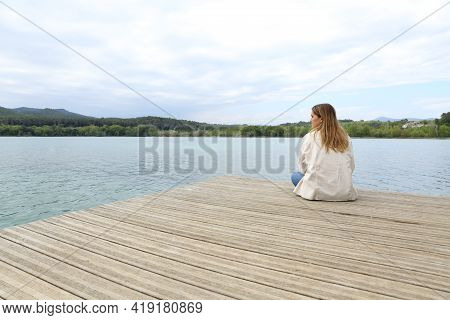Woman Resting Contemplating Views Sitting In A Pier In A Lake