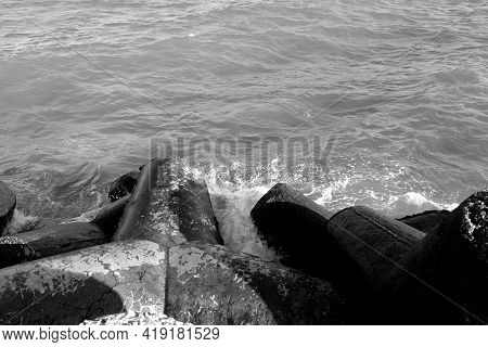 Breakwater Stones On Mole At Black Sea In Black And White. Sea View And Background.