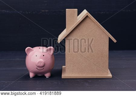 Pink Ceramic Piggy Bank And  House On A Blue Background. Real Estate Rental, Purchase And Sale Conce