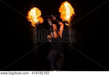 High Energy Firedancer. Sensual Firedancer Twirl Flaming Baton In Darkness. Fire Performance.