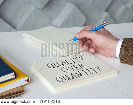 Man Writes Phrase Quality Over Quantity On The Page.