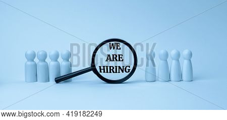 Wooden Figures Of Men Stand On A Blue Background And A Black Magnifying Glass. Recruitment Concept,