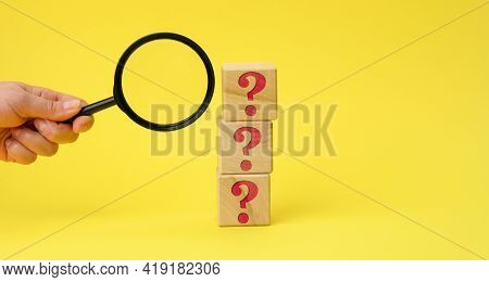 Wooden Cubes With Question Marks And A Female Hand Holds A Magnifying Glass On A Yellow Background.