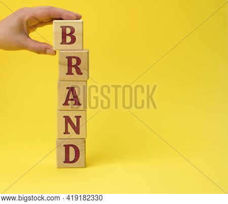 Wooden Blocks With The Inscription Brand On Ayellow Background. Brand Trust Concept For Products, Co