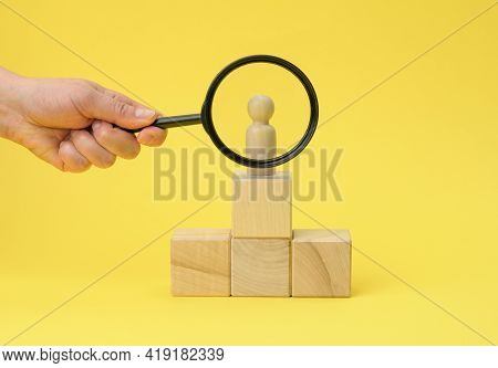Wooden Figurine Of A Man On A Pedestal And A Hand With A Magnifying Glass On A Yellow Background. Th