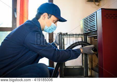 Technician maintaining a pellet stow heater wearing a mask, coronavirus concept