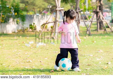Selective Focus. Active Cute Asian Girl Playing Kicking A Blue And White Soccer Ball In The Green La