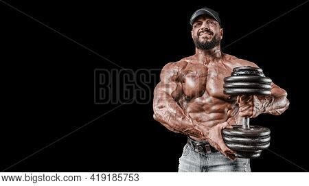 Muscular Athlete Posing In The Studio With Dumbbells. Fitness And Classic Bodybuilding Concept.