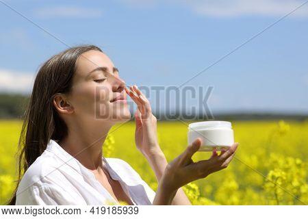Beauty Woman Holding Jar Applying Moisturizer Cream On Face In A Flowered Field