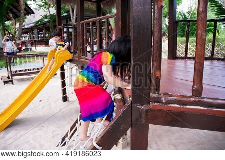 Cute 4 Year Old Asian Girl Is Climbing A Rope Net. The Bottom Floor Is A Sand Pit. A 3 Year Old Boy
