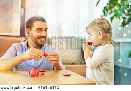 family, fatherhood and childhood concept - happy father and little daughter with toy crockery playing tea party at home
