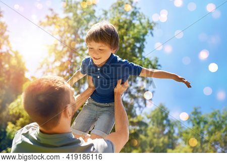 family, fatherhood and people concept - happy father with little son playing in summer park