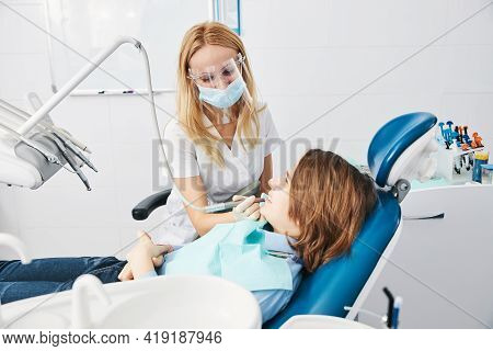 Orthodontist Drilling Boy Side Teeth With Handpiece