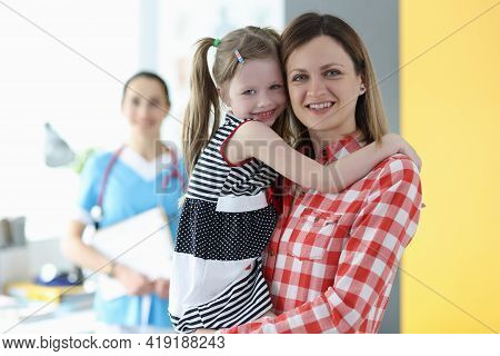 Mom Holding Little Girl In Her Arms At Doctor Appointment