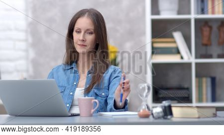 Young woman working online with laptop computer at home sitting at desk. Businesswoman in home office, browsing internet.