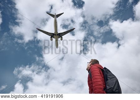 Young Man Looking Up At Flying Airplane Against Cloudy Sky. Themes Nostalgia For Travel And Aviation