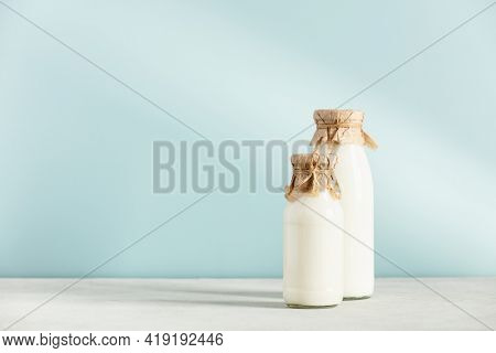 Vegan non dairy plant based milk in bottles on blue background. Alternative lactose free milk substitute, copy space