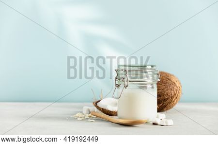 Coconut oil in jar with fresh coconut and tropical leaf shadow on blue background, Spa cosmetic and food ingredient, space for text