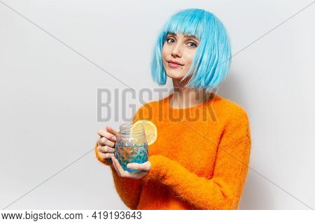 Studio Portrait Of Young Pretty Girl With Blue Bob Hairstyle, Wearing Orange Sweater, Holding Glass
