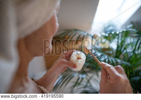 Unrecognizable Senior Woman In Bathroom Brushing Teeth At Home, Ecologic And Sustainabke Lifestyle.