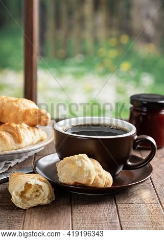 Cup Of Coffee And Croissants On A Rustic Wooden Table By A Window With Rural Background Scene