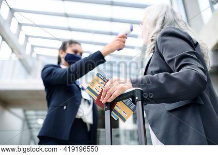Senior Woman In Airport Terminal, Coronavirus, Travel, Measuring Temperature And New Normal.