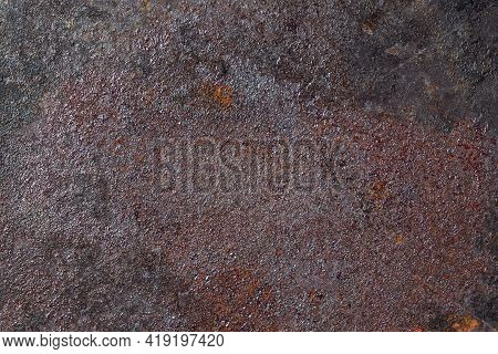 Rust And Soot With Carbon Deposits On The Bottom Of An Old Cast Iron Skillet. Dark Textured Metal Su