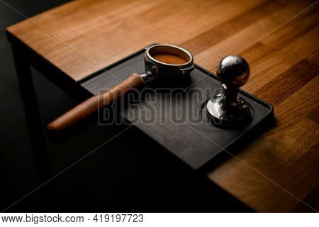 View Of Portafilter With Tamped Coffee And Temper Lying On Black Stand On Wooden Table