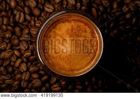 Close-up Top View Of Round Glass With Foamy Coffee Drink On Coffee Beans Background