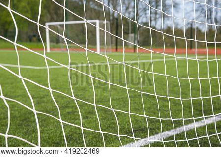 Football Goal On A Green Field Through The Net
