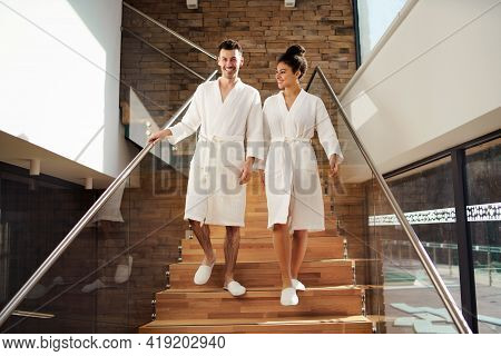 Portrait Of Young Couple In Spa Resort, Walking Down The Stairs.