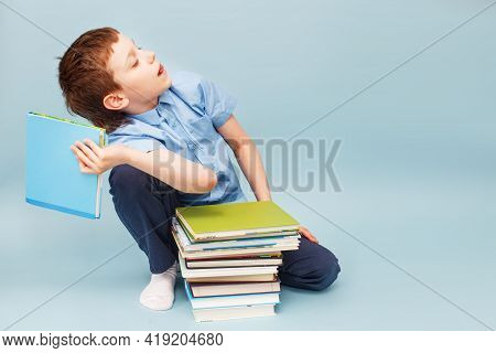Upset Schoolboy Sitting With Pile Of School Books And Throwing A Textbook Isolated On A Blue Backgro