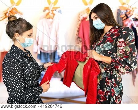 A Young Saleswoman Shows A Customer A Garment Inside A Boutique During The Coronavirus Pandemic. Sub