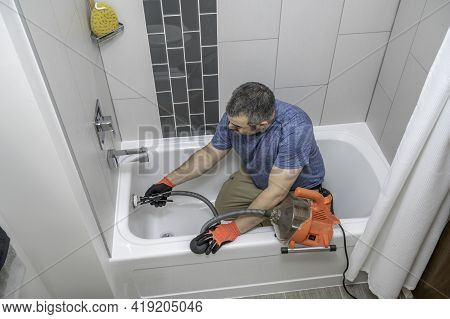 Plumber Drain Cleaning A Bathtub With A Plumbers Snake