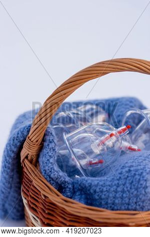 Jars for hijama in a basket in the snow. Wicker basket. Bloodletting according to the Sunnah. Vacuum