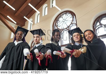 Low Angle View At Multi-ethnic Group Of Young People Wearing Graduation Robes And Pointing Diplomas