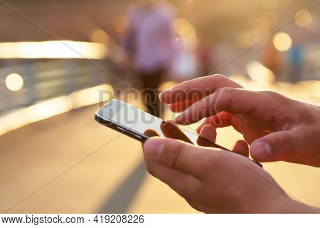 Men Hand Holding Texting Using Mobile Phone Outdoor.