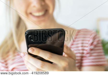 Happy Young Woman Looks Into The Phone And Smiling. Focus On The Smartphone. A Blond Hair Girl Holds