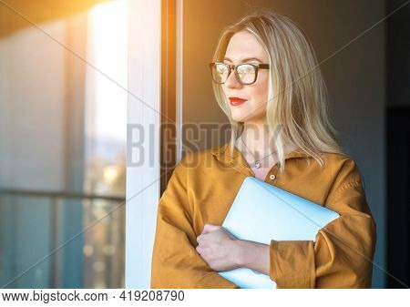 Business woman, learning with laptop, standing on terrace, fresh air, work, study from home. Long distance communication. Staying connected.