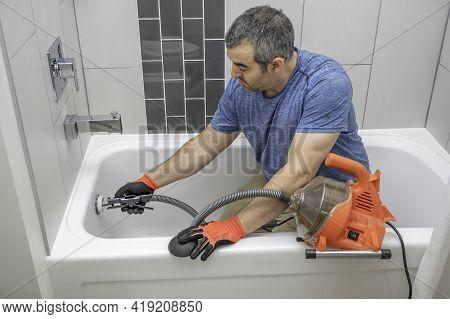 Man Using A Mini Plumbers Snake To Unclog A Bathtub Drain