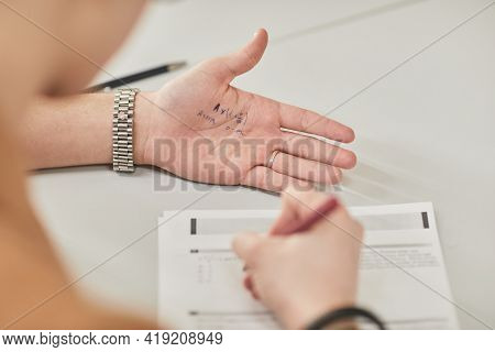 Closeup Of Unrecognizable Student Reading Cheat Note While Taking Exam In School, Copy Space