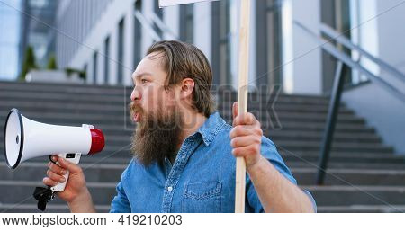 Close Up Of Caucasian Man With Beard Screaming In Megaphone. Male Protestant Holding Table Stop At D