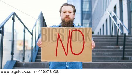 Portrait Shot Of Caucasian Male Activist With Beard Holding Poster No At Demonstration Or Protest. S