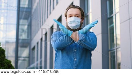 Portrait Shot Of Young Caucasian Man In Medical Mask And Gloves Standing At Street And Showing No Ba