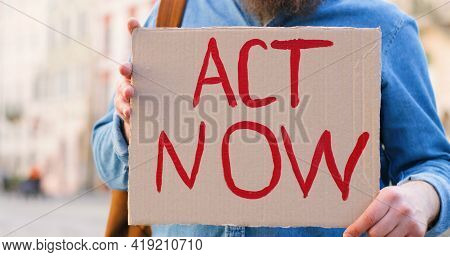 Portrait Of Caucasian Male Activist With Beard Holding Poster Act Now And Megaphone At Political Or
