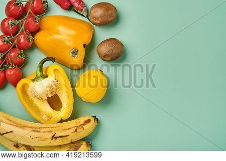 Assortment Of Fresh Pepper, Chili, Bananas, Cherry Tomato, Lemon And Kiwi In Craft Paper Bag Over Gr