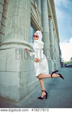 Stunning woman in a white terry dressing gown with a white towel on her head alluring on a city street with a glass of wine and cigarette. Fashion shot. Glamorous lifestyle.
