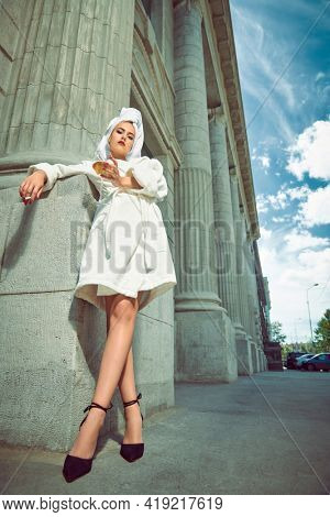 Glamorous woman in a white terry dressing gown with a white towel on her head alluring on a city street with a glass of wine and cigarette. Fashion shot. Glamorous lifestyle.