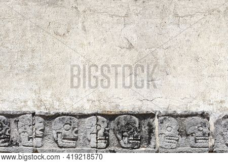 Horizontal banner with stone wall texture and bas-relief carving with human skulls, pre-Columbian Mayan civilization. Day of the Dead (El Dia de Muertos) holiday background. Copy space for text