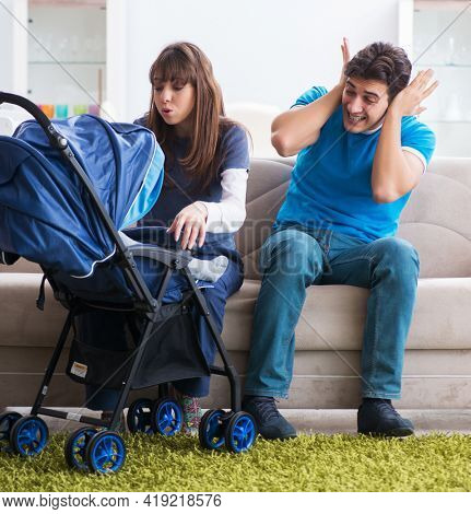 Young parents with their newborn baby in baby pram sitting on th